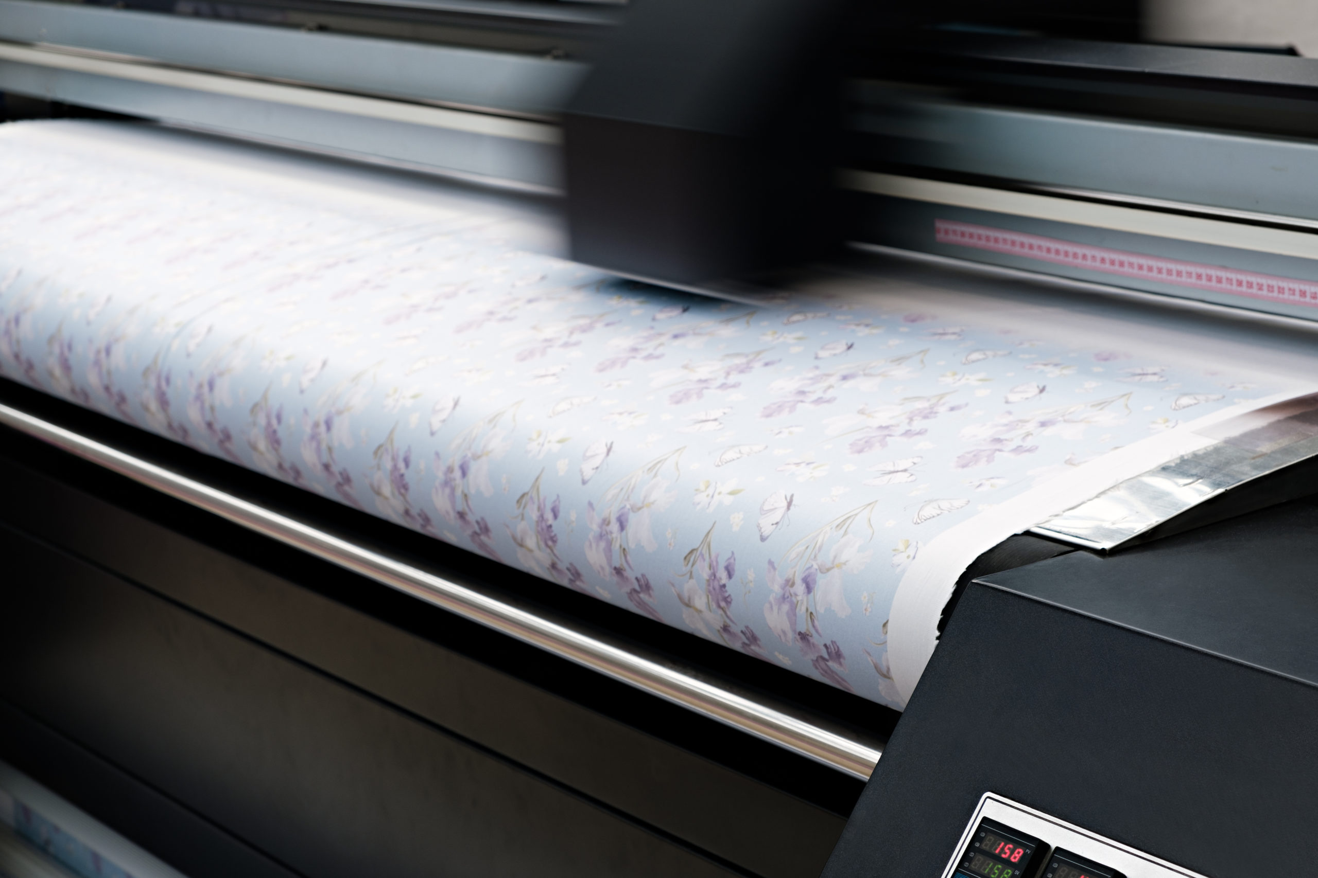 Industrial printing on woven material; modern digital inkjet printer puts a blue pattern picture on a cloth canvas